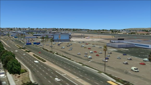One of several large parking lots populated with parked vehicles