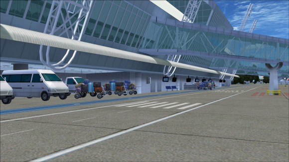 Vehicles and baggage carts along front of terminal building