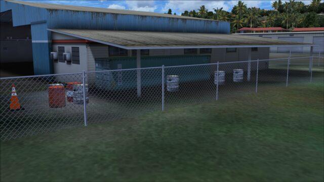 Barrels and fencing near storage building