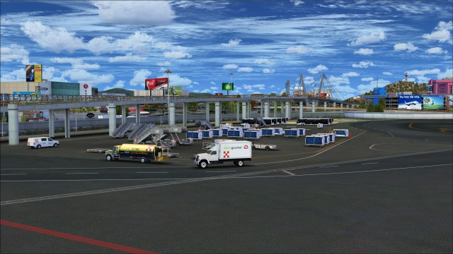 Apron cluttered with service vehicles and baggage carts
